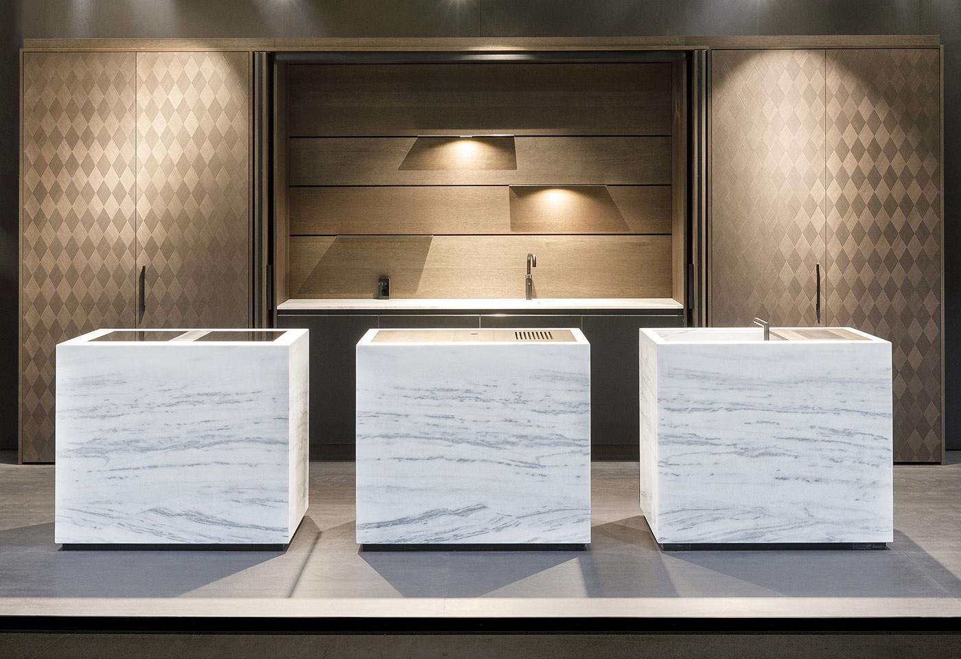 Schliessbare Küchenzeile mit integrierter LED-Rückwand. Im Vordergrund drei Unikate-Marmorblöcke als Kücheninseln